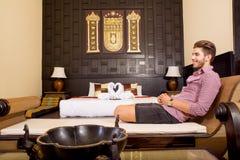 放松在一个亚洲被称呼的旅馆客房的年轻人 免版税库存图片