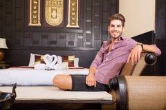放松在一个亚洲被称呼的旅馆客房的年轻人 免版税库存照片