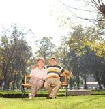 放松在一个公园的成熟夫妇在美好的天 免版税库存图片