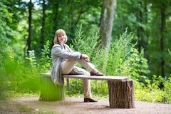 放松在一个夏天公园的美丽的夫人在一个雨天 免版税库存图片