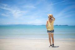 放松在一个完善的海滩的愉快的妇女旅客 免版税库存图片