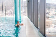 放松在一个室内游泳池的英俊的人 免版税图库摄影