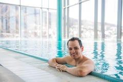 放松在一个室内游泳池的英俊的人 库存图片
