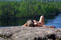 放松在一个岩石的妇女有湖视图 放松在海滨 在天际的监督 免版税库存照片