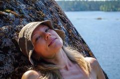 放松在一个岩石的妇女有湖视图 放松在海滨 在天际的监督 免版税图库摄影