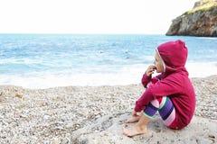 放松在一个有卵石花纹的海滩的女孩 库存照片
