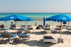放松在一个沙滩的sunbeds的游人在海滩umbrel下 库存照片