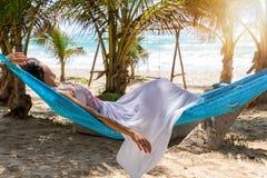 放松在一个热带海滩的一个吊床的妇女 免版税库存照片