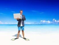 放松在一个热带海滩的商人 图库摄影