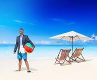 放松在一个热带海滩的商人 库存图片