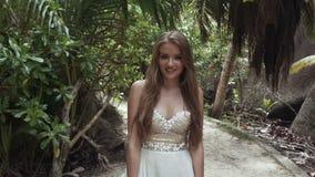 放松在一个热带海滩的豪华礼服的年轻新娘 影视素材