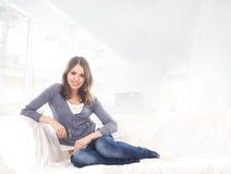 放松在一个白色沙发的牛仔裤的一个少妇 库存图片