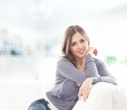 放松在一个白色沙发的牛仔裤的一个少妇 免版税库存图片