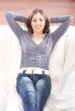放松在一个空白沙发的一名新深色的妇女 库存图片