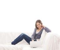 放松在一个空白沙发的一名新白种人妇女 免版税库存图片