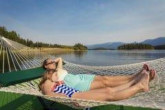 放松在一个美丽的Mountain湖的一个吊床的妇女和孩子 免版税库存图片