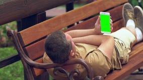 放松在一张公园长椅的人在阳光下 股票视频