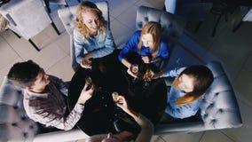 放松在一张桌上的小组青年人在咖啡馆或餐馆,饮用的酒,聊天 在视图之上 股票录像