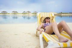 放松在一张躺椅的美丽的妇女一个热带海滩假期 免版税库存图片