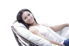 放松在一把圆的舒适软的椅子的现代少妇 免版税库存图片