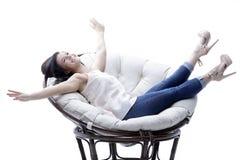 放松在一把圆的舒适软的椅子的现代少妇 免版税图库摄影