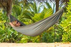 放松在一种热带手段的吊床的年轻美丽的妇女 免版税库存照片