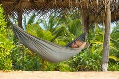 放松在一种热带手段的吊床的年轻美丽的妇女 库存照片