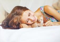 放松在与一只非常逗人喜爱的小猫的一张床上的妇女 免版税库存图片