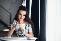 放松在与一杯茶的一个咖啡馆的微笑的妇女 愉快的偶然女性饮用的咖啡和看照相机 免版税库存图片
