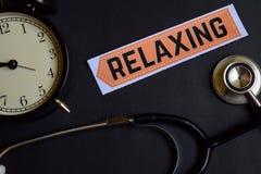 放松在与医疗保健概念启发的本文 闹钟,黑听诊器 免版税库存图片