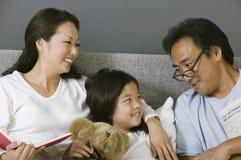 放松在与女儿的床上的母亲和父亲 免版税库存图片