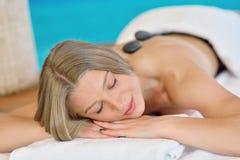 放松在与热的石头的温泉沙龙的美丽的妇女在身体 秀丽治疗疗法 免版税库存照片