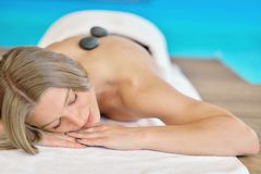 放松在与热的石头的温泉沙龙的美丽的妇女在身体 秀丽治疗疗法 库存照片