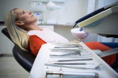 放松在与牙齿工具的牙医椅子的妇女在前景 库存图片