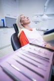 放松在与牙齿工具的牙医椅子的妇女在前景 免版税库存图片