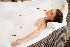 放松在与玫瑰花瓣的泡末浴的妇女 机体关心英尺健康温泉水妇女 库存图片