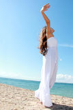 放松在与胳膊的海滩的妇女打开享受她的自由 库存图片