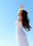 放松在与胳膊的海滩的妇女打开享受她的自由 免版税库存图片