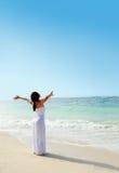 放松在与胳膊的海滩的妇女打开享受她的自由 免版税图库摄影