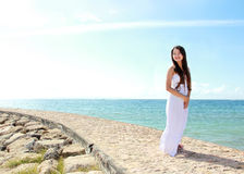 放松在与胳膊的海滩的妇女打开享受她的自由 图库摄影