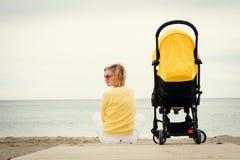 放松在与婴儿车的海滩的年轻母亲 免版税库存照片