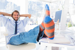 放松在书桌的设计师没有鞋子和微笑 免版税库存照片
