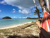 放松在五颜六色的吊床的椰子树树荫下 库存照片