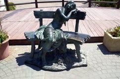 放松在位子的女孩的雕塑在马尔韦利亚海滩,安大路西亚,西班牙,欧洲 免版税图库摄影
