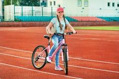 放松在体育场的十几岁的女孩 女孩生活方式乘自行车 库存图片
