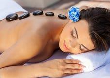 放松在健康温泉的妇女有热的石治疗按摩 免版税库存照片