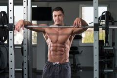 放松在健身房的一个肌肉人的画象 库存照片