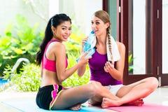 放松在健身锻炼以后的妇女朋友 免版税库存照片