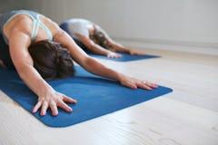 放松在儿童姿势的两名妇女做瑜伽 免版税库存照片