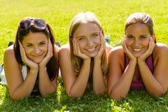 放松在公园微笑的朋友的青少年的妇女 免版税库存照片